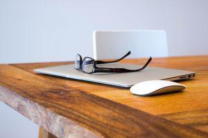 Foto: Brille liegt auf geschlossenem Macbook auf brauem Holztisch