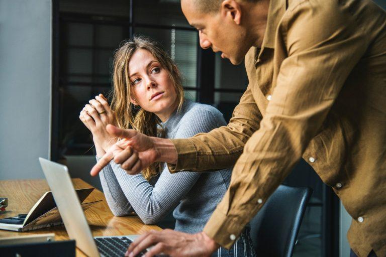 Foto: Man in braunem Hemd instruiert eine Frau am Laptop