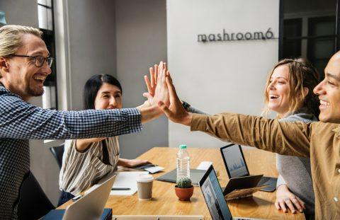 Foto von 4 Business-Leuten am Schreibtisch, die in die Hände klatschen