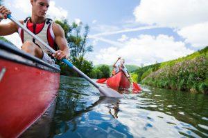 Zwei Kanu-Fahrer auf Fluss vor blauem Himme