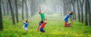 Vier Kinder springen auf grüner Wiese