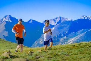 Foto: Joggender Jungen in weißem T-Shirt vor Mann mit orangem T-Shirt im Gebirge