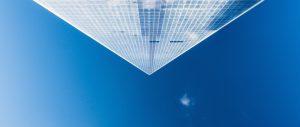 Foto einer pyramidenförmigen Glasfassade vor einem blauen Himmel