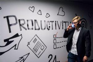 Junger Mann im Sacko mit Smartphone vor einer weißen Wand mit der Aufschrift Productivity