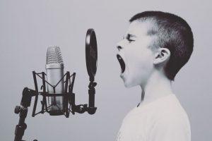 Schwarz-weiß Fotografie eines Jungen mit kurzen Haaren der in ein Mikrofon schreit