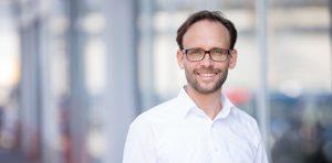 Portrait von Sean Kollak im weißen Hemd vor Glasfassade