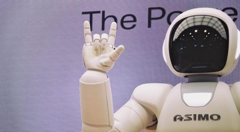 Weißer Roboter mit schwarzem Visier hebt Hand zum Gruß
