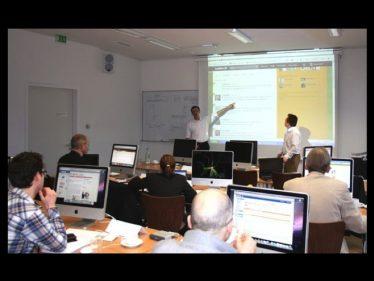 Foto: Sean Kollak in einem Seminarraum vor Leinwand und Teilnehmer vor Monitoren