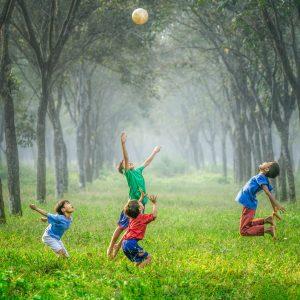 Vier Kinder springen auf grüner Wiese nach einem Ball